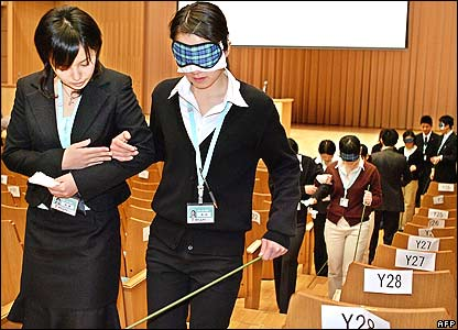 Employees guide colleagues during a training session in Tokyo, Japan