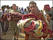 Iraqi men hold the bodies of their dead children in Balad