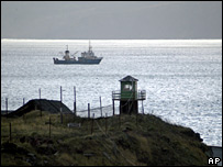 A Russian guard tower on Kunashir island, with a fishing boat at sea (file photo)