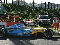 Alonso's car passes the stranded Ferrari of Schumacher