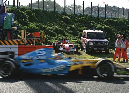 Fernando Alonso passes Michael Schumacher's stricken Ferrari in the closing stages of the Japanese Grand Prix