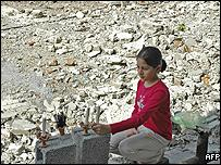 A Pakistani relative of the earthquake victims lights a candle on the site of the Margalla apartment towers which collapsed in the quake