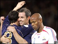 Scotland's David Weir embraces goalscorer Gary Caldwell as France's Boumsong contemplates defeat