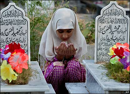A girl prays over the graves of her brothers who died in last year's earthquake