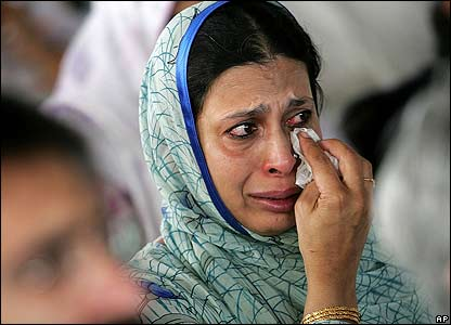 A woman wipes tears from her eyes during a memorial ceremony in Islamabad