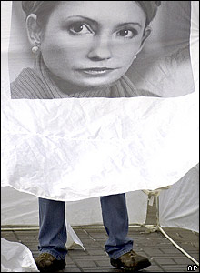 A campaign worker with a poster of Ukraine opposition leader Yulia Tymoshenko