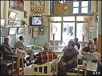 Iraqis in a Baghdad cafe watch Saddam's trial on television
