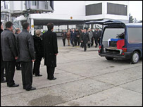 Officials stand as the coffin is placed in the hearse