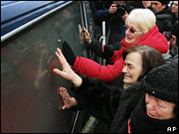 Women touch the hearse carrying Mr Milosevic's coffin