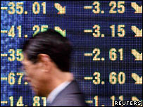 A man walking past a share price board