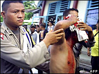 Indonesian policeman helps a colleague after clash - 16/3/06