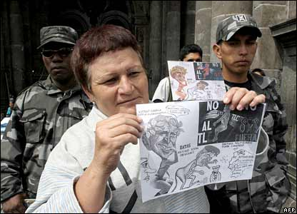 An Ecuadorian woman holds a caricature of US President George W Bush in Quito