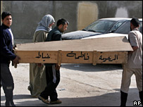 Two men carry a wooden coffin