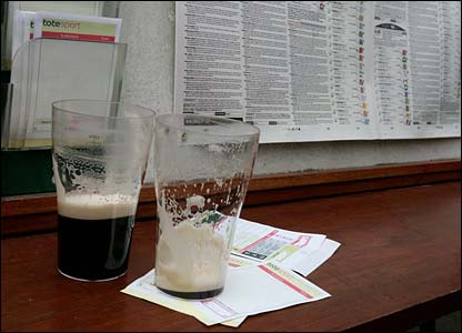 Half-full pints of stout and unused betting slips at Cheltenham