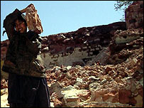 A boy lifting the rubble