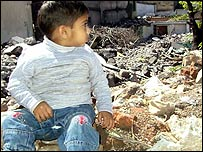 Child sits atop a pile of rubble