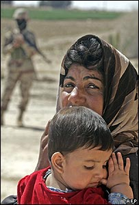 Iraqi woman hold child as Iraqi soldier stands nearby by road north of Baghdad