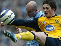 Antoine Sibierski (l) challenges Wigan's Leighton Baines