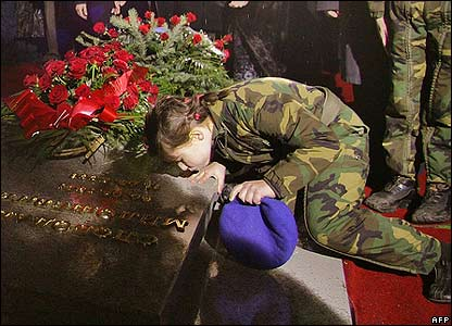 Girl in military uniform kisses Mr Milosevic's tombstone
