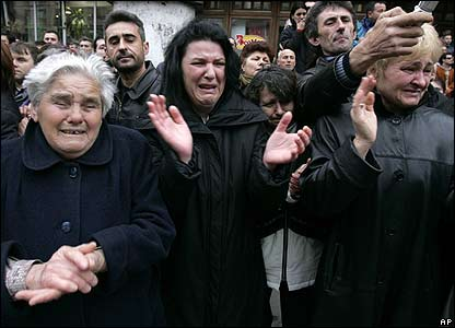 Mourners watch the coffin pass by in Pozarevac