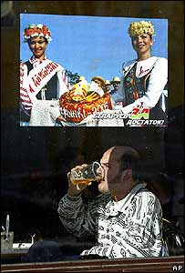 Man drinks beer under a pro-Lukashenko poster in Minsk