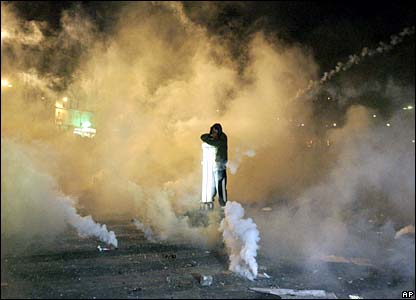 A protester stands amid clouds of tear gas in Paris, France