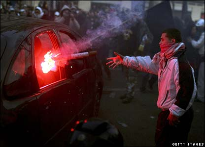 A student throws a flare into a parked car in Paris, France