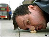 Mark McGowan pushing a nut with his nose