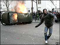 Man throwing stones in front of burning car