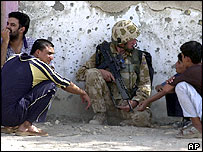 British soldier talks to Iraqis while on patrol in Basra - September 2004