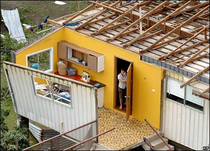 A woman phones for help from her roofless house