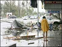 A man outside damaged shops on the main street in Innisfail, Queensland