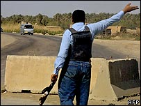 Iraqi police direct people away from the scene of a clash in Miqdadiya