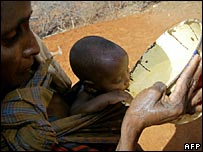 A woman gives her child water in drought-stricken Wajir district in Kenya's north-eastern province
