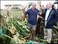 Prime Minister John Howard (r) looks at a ruined banana crop in Innisfail