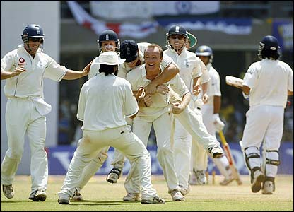 Udal is mobbed by his England team-mates after removing Mahendra Dhoni