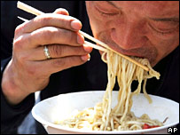 Man eating noodles with disposable chopsticks
