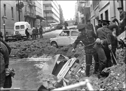 Spanish policemen clear bomb debris in December 1973