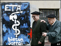 Men walk past Eta graffiti