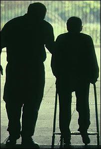 Hombre en la tercera edad asistido por un enfermero