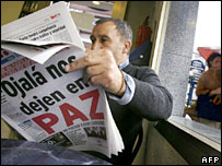 "Man reads Spanish newspaper with headline ""Peace"""