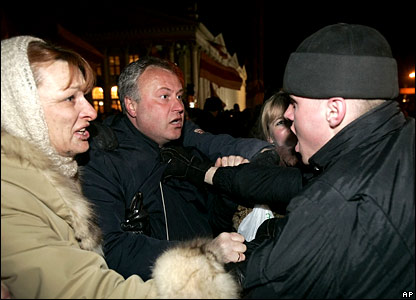 A woman argues with a police officer as he tries to detain a man
