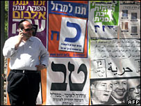 An Israeli walks past election posters