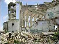 Gunman walks past ruined building