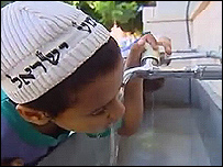 A boy drinking water from a tap