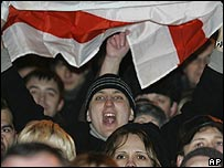 A protester holds a banned Belarusian flag during a rally in Minsk