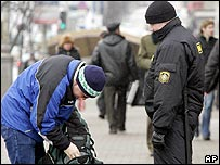 Belarusian police inspect a man's bag near opposition protests in Minsk