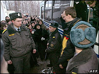 Friends and relatives look on as police take away arrested protesters in Minsk