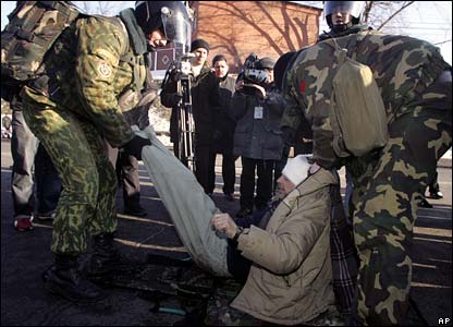 Belarussian soldiers carry an injured protesters