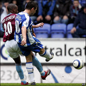 Wigan's Lee McCulloch shoots under a challenge by Nigel Reo-Coker